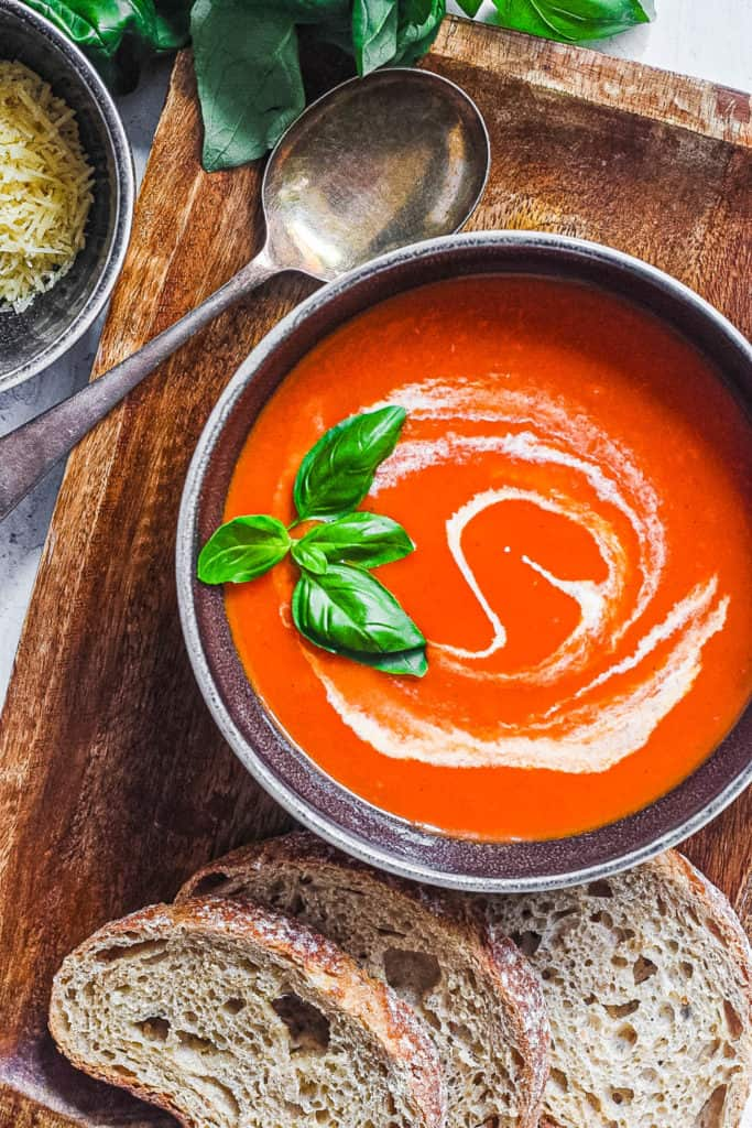 easy instant pot tomato soup (keto tomato soup) with basil and cream served in a black bowl