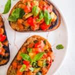 easy vegan bruschetta with tomatoes and white beans on a plate topped with basil