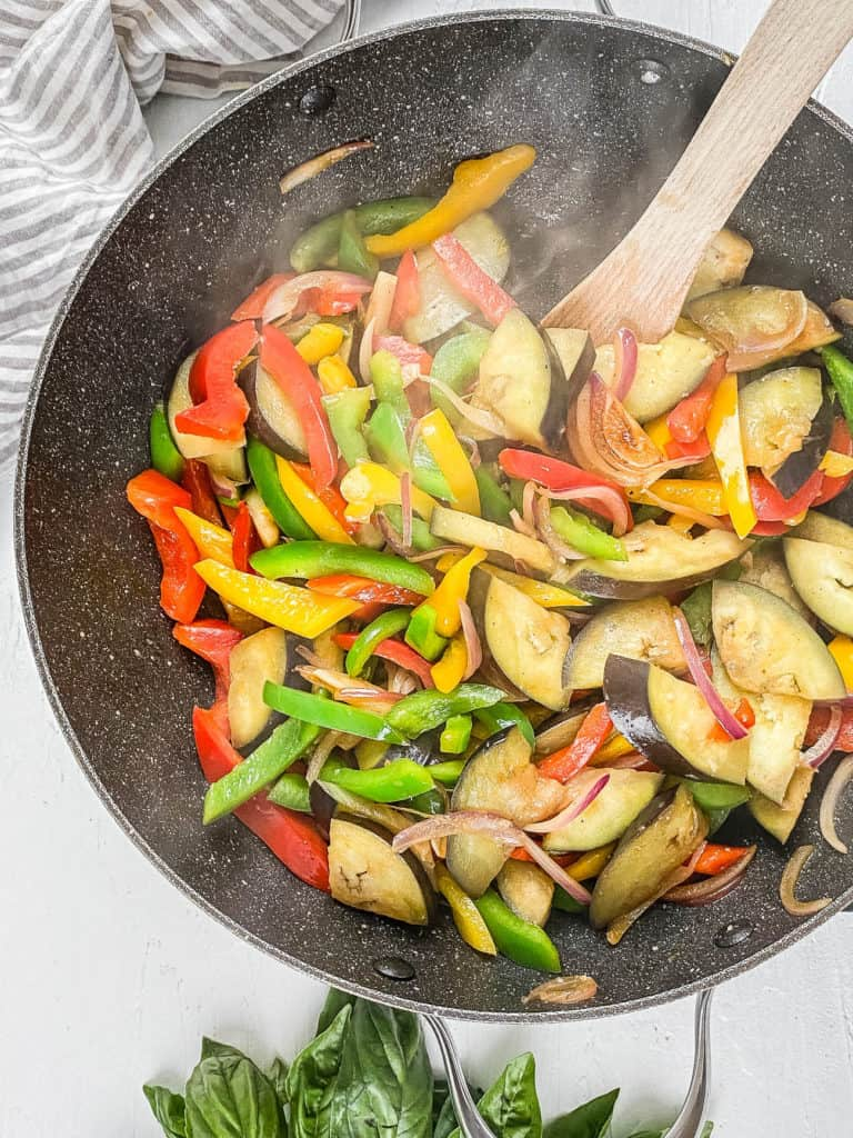 bell peppers and eggplant cooking in a wok