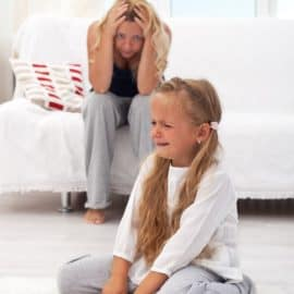 Mom with head in her hands as daughter has a tantrum on the floor.