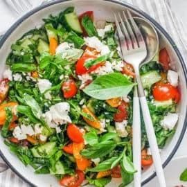 tomato avocado cucumber salad in a white bowl