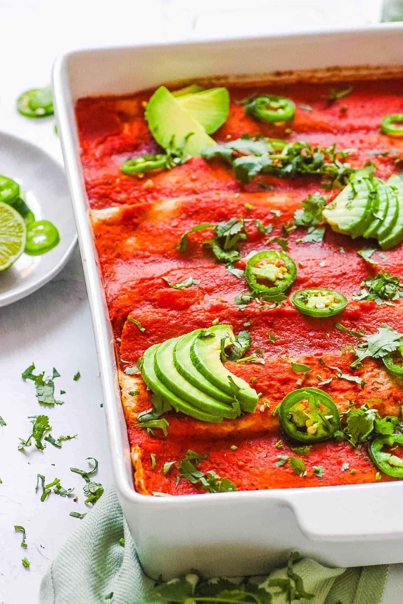 easy healthy vegan enchilada casserole recipe topped with avocado and jalapeno