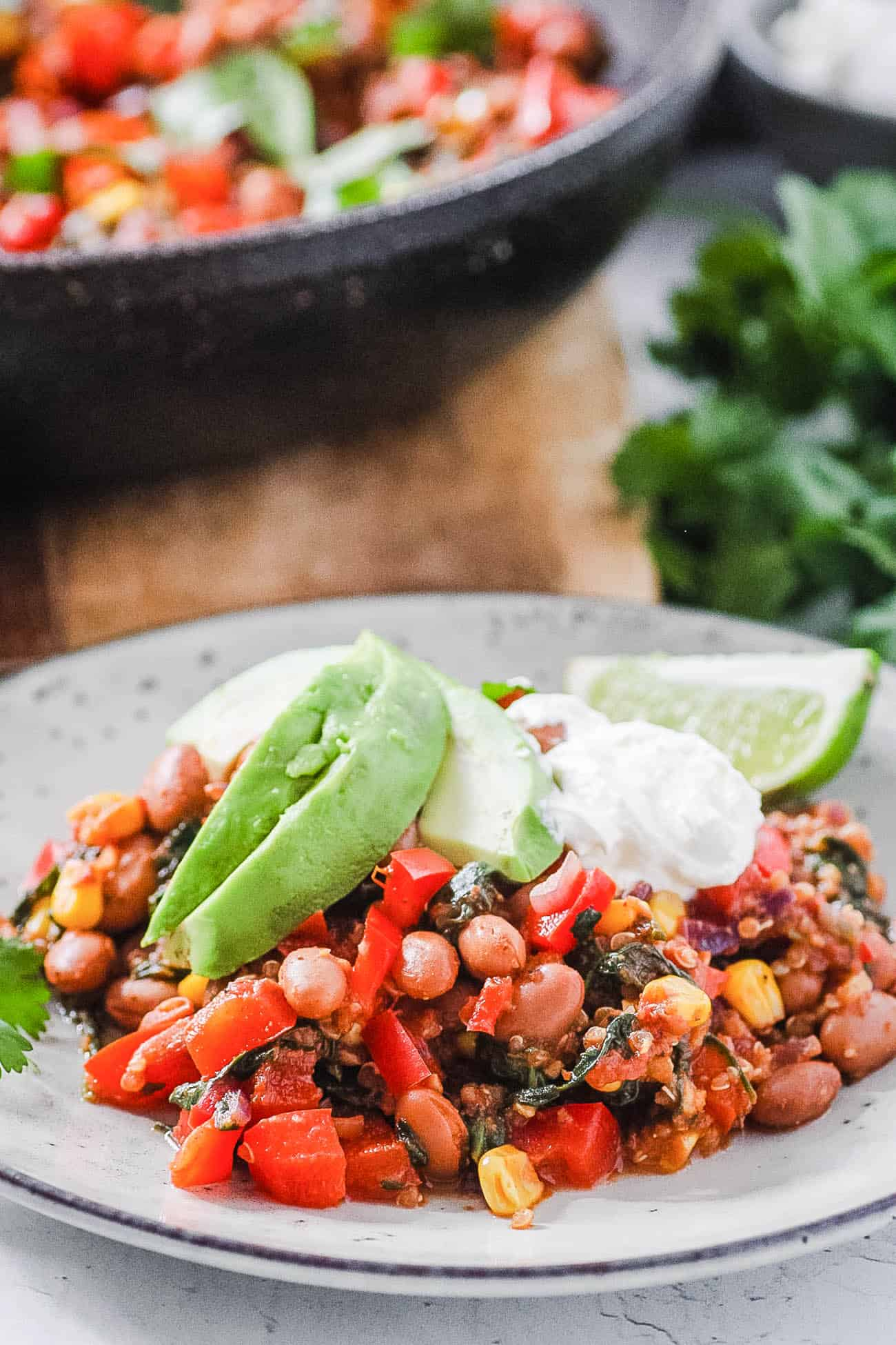 vegan pinto bean casserole on a plate with avocado and lime