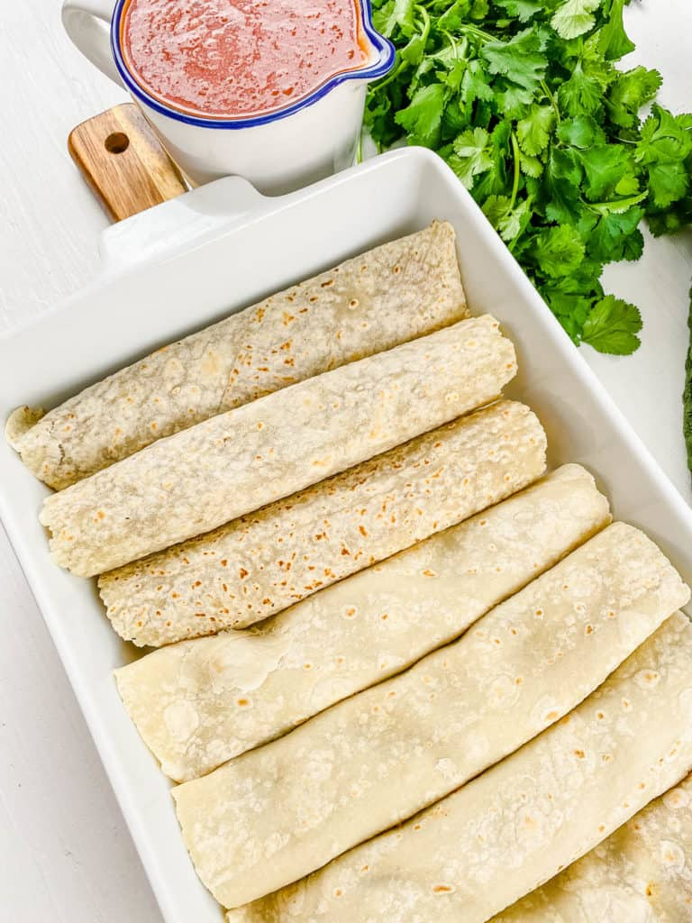 rolled up enchiladas in a baking dish