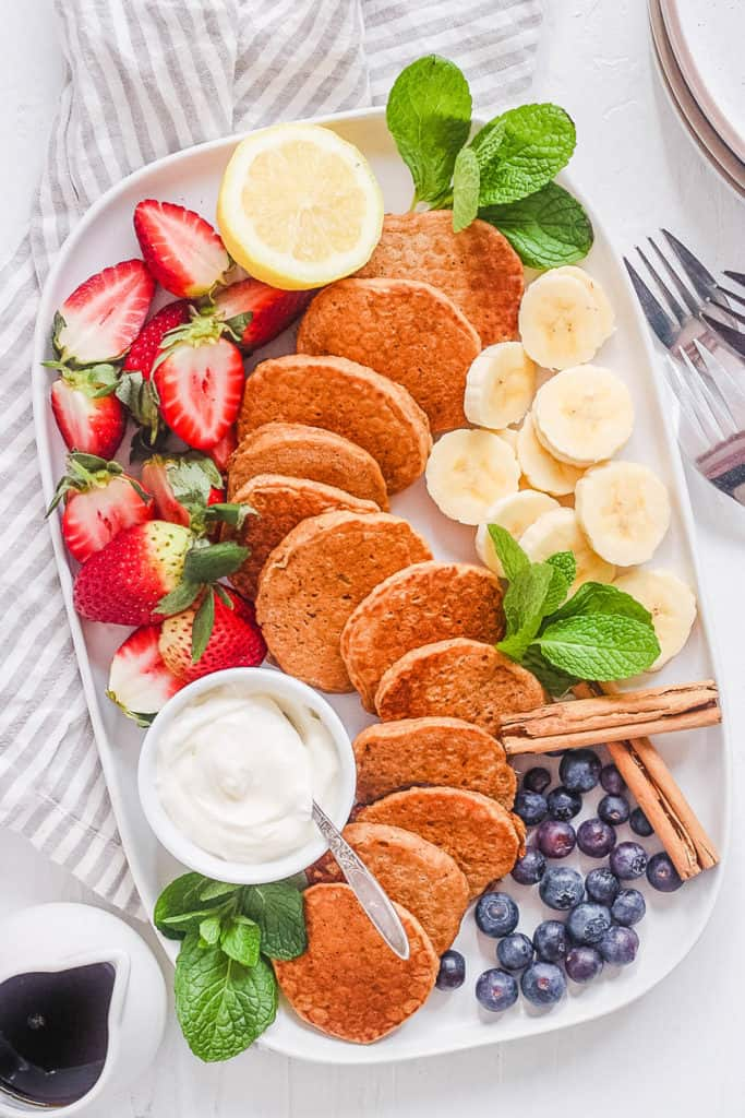 thick and fluffy mini pancakes - silver dollar pancakes recipe on a white plate with fresh fruit
