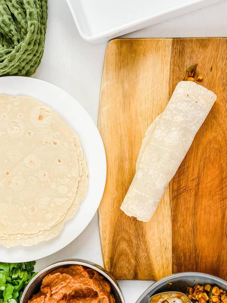 corn tortilla rolled up on a cutting board