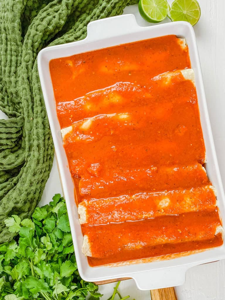 sauce added on top of enchiladas in a baking dish